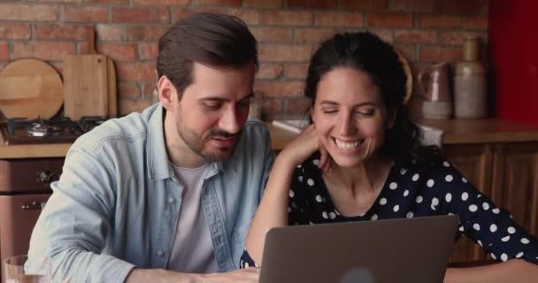 Atraktivní pár sedět v kuchyni pomocí notebooku diskutovat online nákup