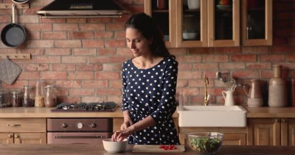 Žena stojící v kuchyni krájí cherry rajče pro zeleninový salát