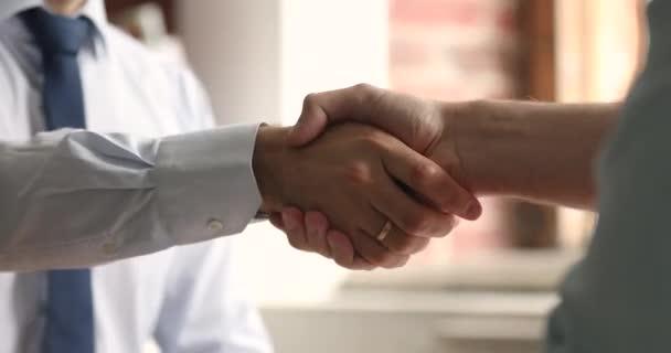 Dva obchodní partneři se setkají v kanceláři a potřesou si rukama detailně
