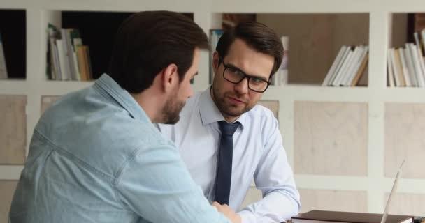 Zwei Kollegen sitzen mit Laptop am Schreibtisch und diskutieren Online-Präsentation