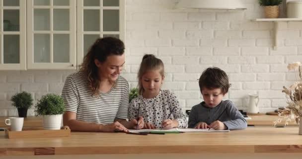 Mutter und Kinder reden und zeichnen mit Bleistift am Skizzenbuch