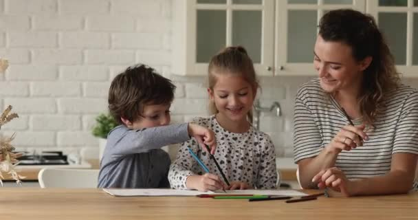 Mother and children talking and drawing with pencils at sketchbook