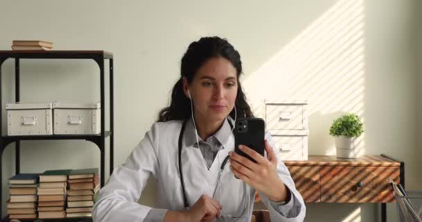 Qualifizierte junge Allgemeinmedizinerin hält mobiles Videotelefon.