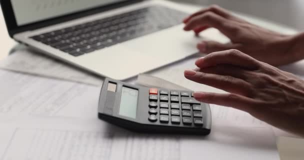 African female calculates expenses, pay bills through e-bank on laptop