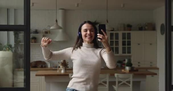 Nő zenét hallgatni a fülhallgatón keresztül tartja okostelefon segítségével digitális szolgáltatások