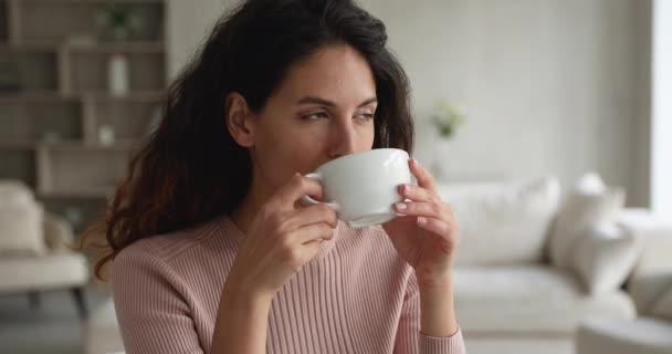 Glückliche junge hispanische Frau trinkt zu Hause eine Tasse Tee.