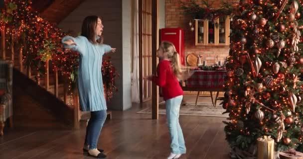 Glückliche kleine verrückte entzückende Mädchen tanzen mit fürsorgliche Mutter.