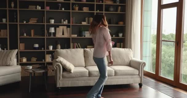 Carefree young lady dance on warm floor at living room