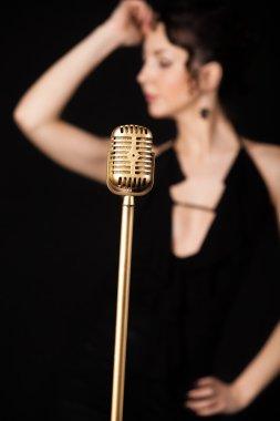 Beautiful slim girl vocalist behind golden vintage microphone