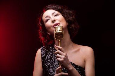 Beautiful girl singer singing lyric song with retro microphone