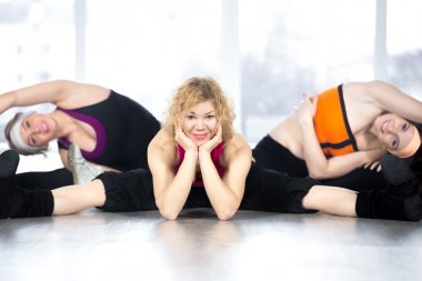 Group of three females doing stretching fitness exercises in cla
