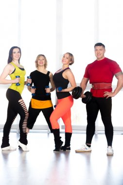 Group of positive sporty bodybuilders doing weight training in g