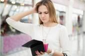 Zmatená mladá žena kontrola kabelku poté, co strávil příliš mnoho