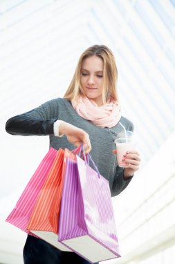 Young woman in a hurry checking time after shopping