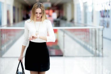 Young business woman in a rush, glancing at time on wristwatch