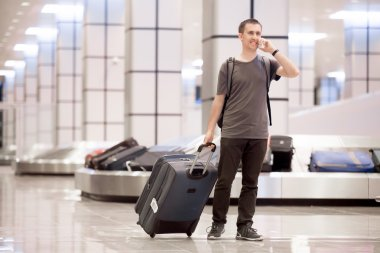 Traveller at conveyor belt on phone