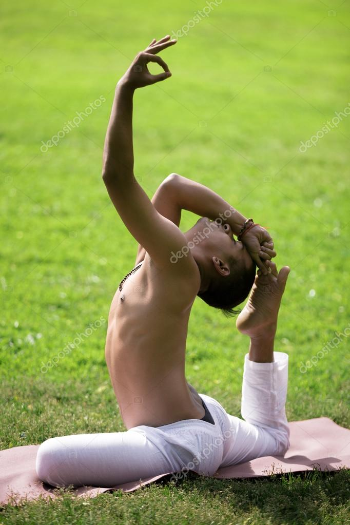 Serene attractive Indian young man in white pants doing stretching sport, yoga, fitness or pilates exercises on green lawn, One Legged King Pigeon Pose with hand in jnana mudra