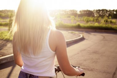 Young woman on bicycle in sunlight