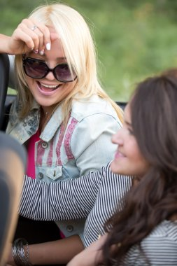 Young women laughing in car