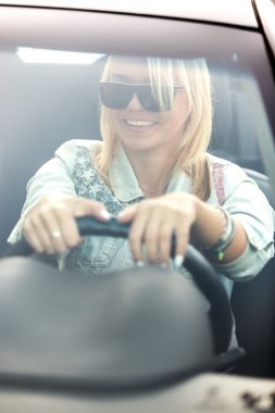 Young cheerful woman driving