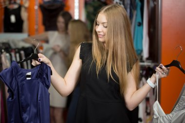 Smiling woman choosing between two garments in shop