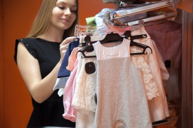 Young mother choosing baby clothes