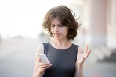 Young business woman irritated with her phone