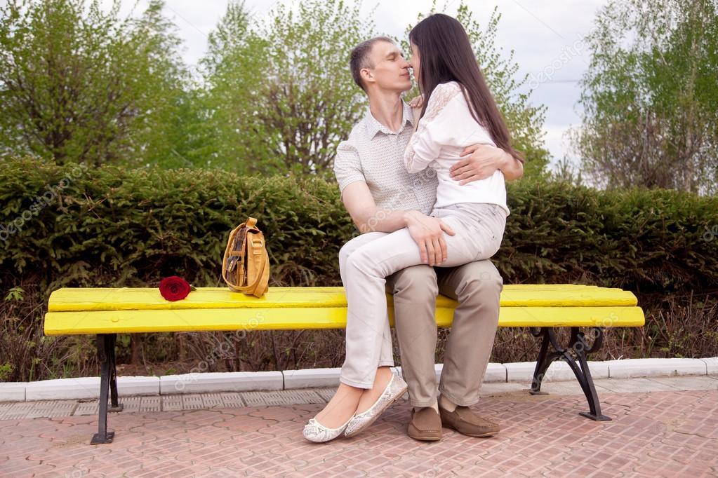 couple kissing on bench stock photo fizkes 86804316