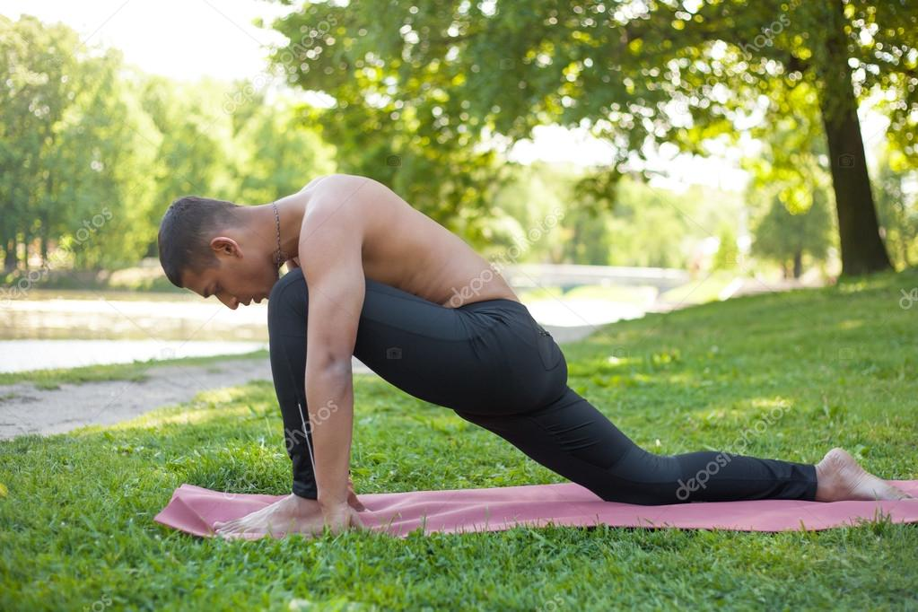 Profile of sporty Indian young man working out, doing stretching training for legs, low lunge exercise on lake in park, resting after anjaneyasana, full length