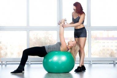 Women doing pilates exercises in gym