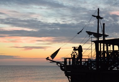 Silhouette of a pirate ship at sunset