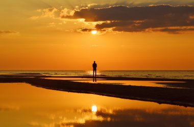 Silhouette of a man watching sunset on a seashore