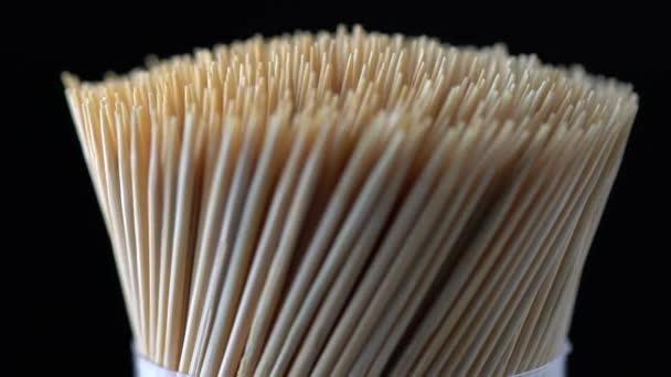 Makró zárja le a fa bambusz fogpiszkálókat, oldalról lassított mozgású forgás. Fogápolás fogápolás fogápolás fogápolás étkezés után. Szájüregmegelőzés. Fogászati ellátás.