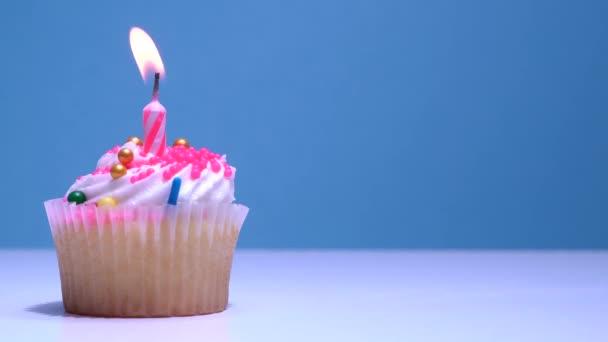 Süti egy szülinapi gyertya égő és cukor cukormáz a kék háttér. Finom muffin dekoráció. Házi készítésű vaníliás kalács vajkrém cukormázzal. Sekély mélységélesség.
