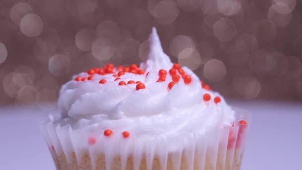 Aranyos cupcake makró sekély mélysége mező nézet. Finom desszert muffin a lány születésnapjára vagy Valentin napra. Díszített cukor megszórja csésze torta fehér vanília krém arany háttér.