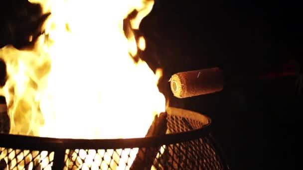 Fire staff prop lights off fire pit against black background in slow motion (120 fps)