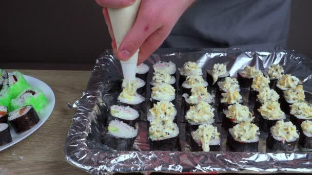 Mladý kuchař se učí vařit závitky z různých produktů, dělat závitky a sushi doma, japonské jídlo koncept