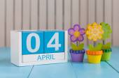April 4th. Image of april 4 wooden color calendar on white background with flowers. Spring day, empty space for text. Webmaster Day