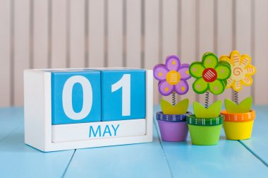 May 1st. Image of may 1 wooden color calendar on white background with flowers. Spring day, empty space for text.  International Workers Day