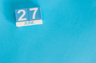 June 27th. Image of june 27 wooden color calendar on blue background. Summer day. Empty space for text. International fisheries Day