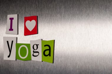 I Love Yoga written with color magazine letter clippings on metal background. Concept of sport and healthcare life. Empty space