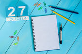 Photo October 27th. Image of October 27 wooden color calendar on blue background. Autumn day. Empty space for text
