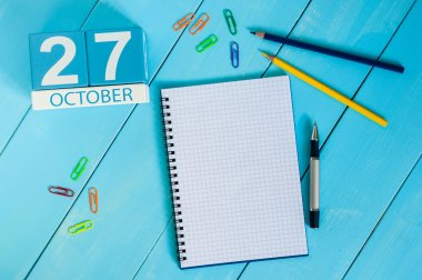 October 27th. Image of October 27 wooden color calendar on blue background. Autumn day. Empty space for text