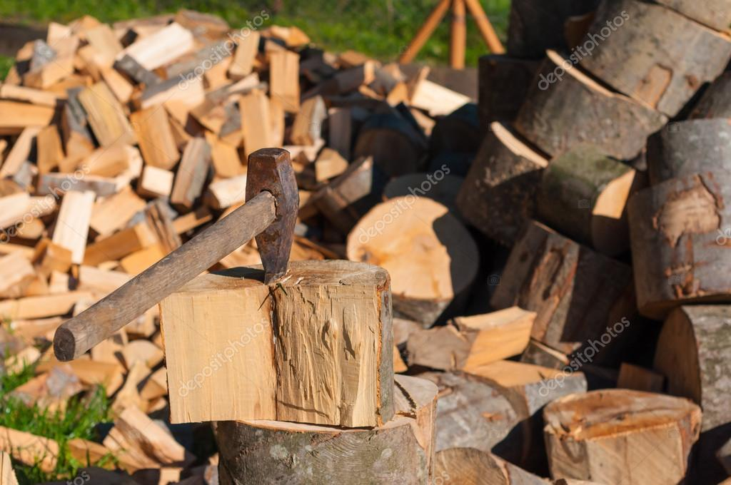 Axe in Chopping Block and Firewood. Ax pile of chopped firewood