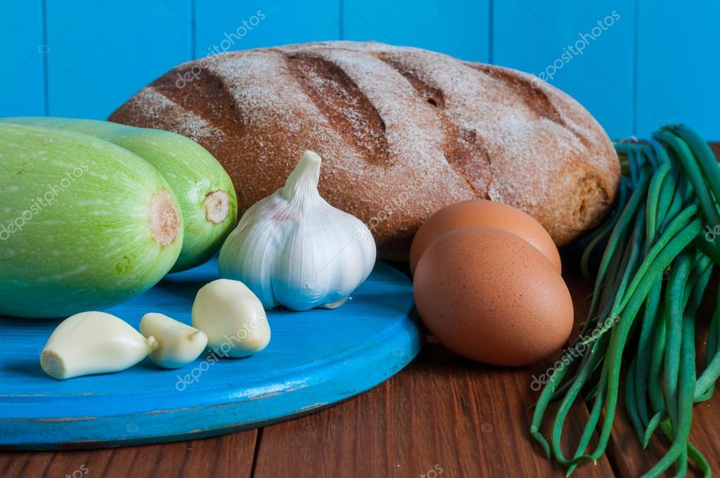 Bread, vegetable marrow in rural or rustic kitchen. Dough recipe ingredients eggs, onion, garlic, squash on vintage wood table from above.