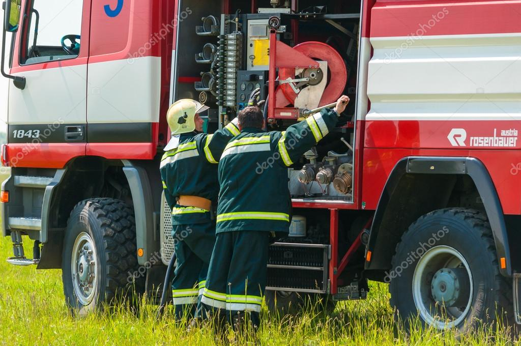BORYSPIL, UKRAINE - MAY, 20, 2015: Firefighter lifted the Red hose after training put off the fire at Boryspil International Airport, Kiev, Ukraine.