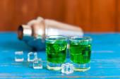 Fotografie Closeup von zwei grüne Absinth Alkohol Aufnahmen mit Eiswürfel und Shaker auf hölzernen Hintergrund