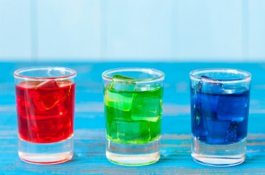 Three kinds of alcoholic drinks in shot glasses on bar counter and light background