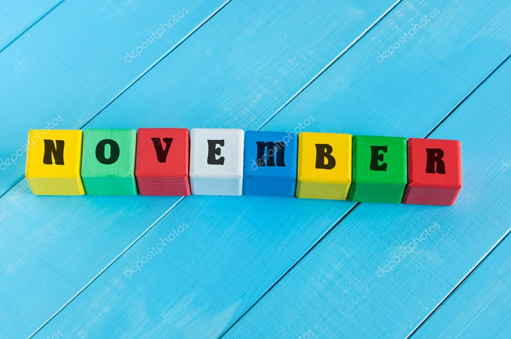 Word November on color wooden cubes with light blue wood background