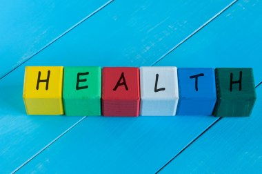 Health - word on childrens colourful cubes or blocks. Colourful wooden background